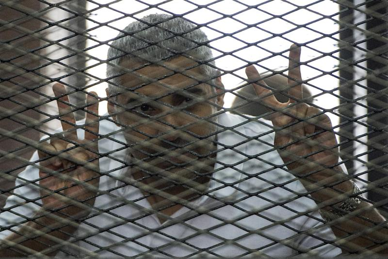 Al-Jazeera news channel's Egyptian-Canadian Mohamed Fadel Fahmy listens to the verdict inside the defendants cage during his trial for allegedly supporting the Muslim Brotherhood on June 23, 2014 at the police institute near Cairo's Tora prison (AFP Photo/Khaled Desouki)