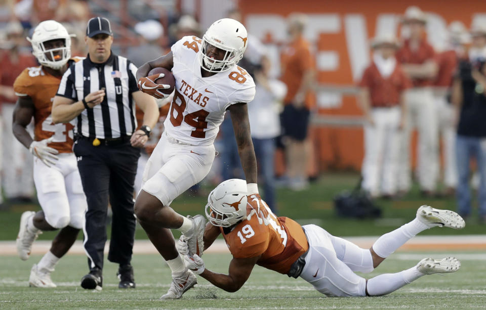 Texas wide receiver Lil'Jordan Humphrey (84) leaps out of the grasp of Texas Longhorns defensive back Brandon Jones (19) during the team's Orange-White intrasquad spring college football game, Saturday, April 21, 2018, in Austin, Texas. (AP Photo/Eric Gay)