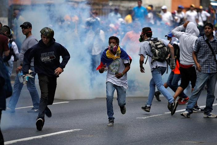 <p>Demonstrators run away from tear gas fired by security forces during an opposition rally in Caracas, Venezuela April 6, 2017. (Photo: Carlos Garcia Rawlins/Reuters) </p>
