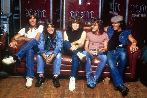 Photo of Cliff WILLIAMS and Angus YOUNG and Brian JOHNSON and AC/DC and Malcolm YOUNG and Simon WRIGHT and AC DC; L-R: Cliff Williams, Malcolm Young, Simon Wright, Angus Young, Brian Johnson - posed, group shot, in front of flight cases, c.1984/1985