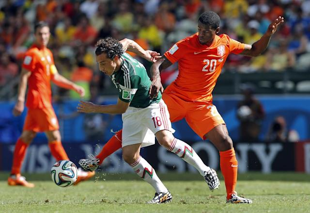 Netherlands' Georginio Wijnaldum, right, holds off Mexico's Andres Guardado during the World Cup round of 16 soccer match between the Netherlands and Mexico at the Arena Castelao in Fortaleza, Brazil, Sunday, June 29, 2014. (AP Photo/Wong Maye-E)