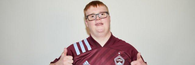 Special Olympian and soccer player Scotty Stephens, a white man with Down syndrome, wearing a maroon jersey and giving two thumbs up
