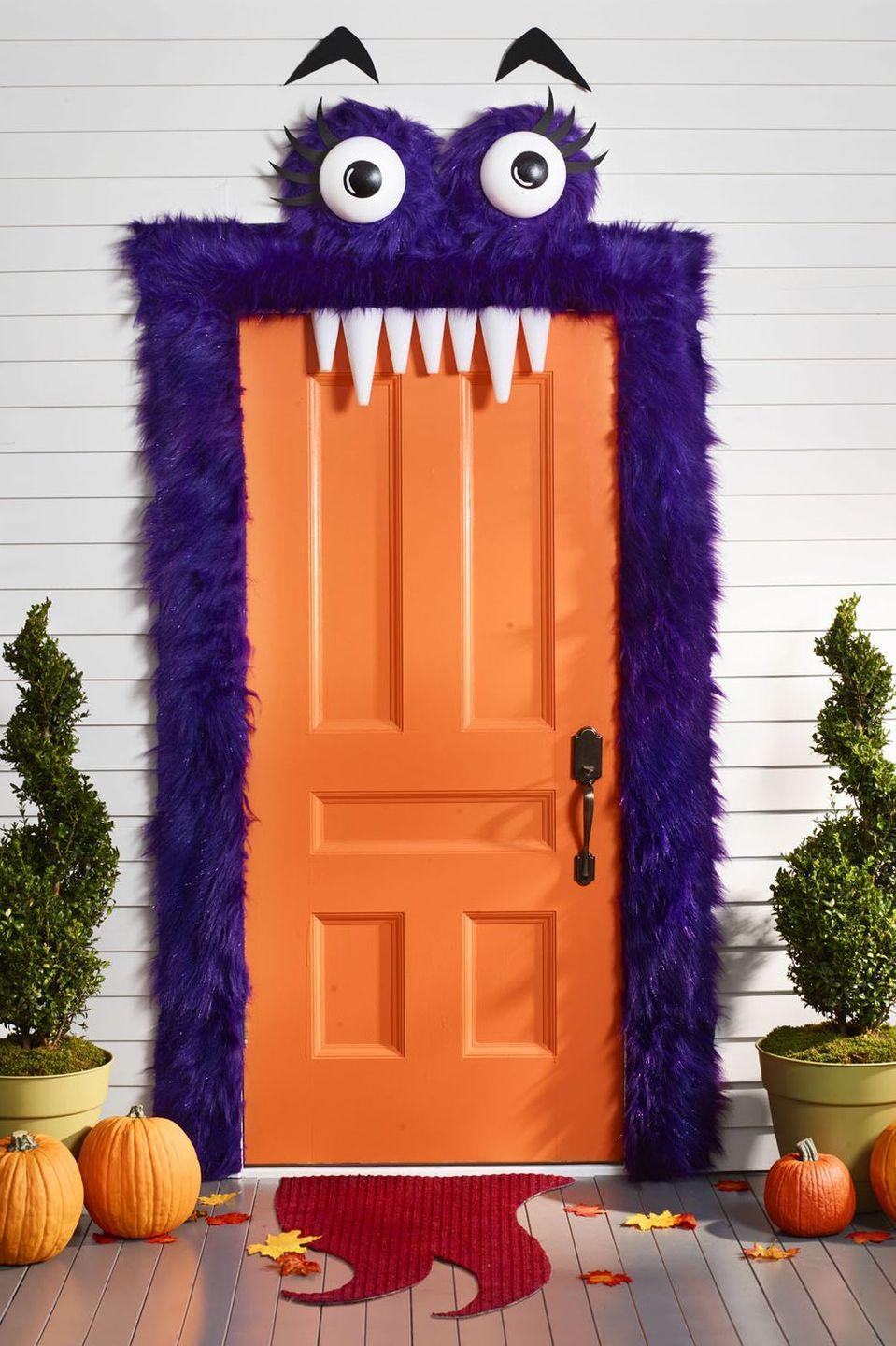 """<p>This quirky DIY entryway will make everyone giggle. To make the eyes, paint black circles on two <a href=""""https://www.amazon.com/Inch-Half-Round-Styrofoam-Polystyrene/dp/B07SQ7736X/ref=sr_1_3?tag=syn-yahoo-20&ascsubtag=%5Bartid%7C10055.g.4602%5Bsrc%7Cyahoo-us"""" rel=""""nofollow noopener"""" target=""""_blank"""" data-ylk=""""slk:8-inch foam half balls"""" class=""""link rapid-noclick-resp"""">8-inch foam half balls</a>. Cut black foam eyelashes and eyebrows from black construction paper. From three yards of <a href=""""https://www.amazon.com/Barcelonetta-Supply-Costume-Decoration-Purple/dp/B07W8HSQHR/?tag=syn-yahoo-20&ascsubtag=%5Bartid%7C10055.g.4602%5Bsrc%7Cyahoo-us"""" rel=""""nofollow noopener"""" target=""""_blank"""" data-ylk=""""slk:faux purple fur"""" class=""""link rapid-noclick-resp"""">faux purple fur</a>, cut two 16-inch squares and hot-glue each around a <a href=""""https://www.amazon.com/Craft-Foam-Wreath-Polystyrene-Decorations/dp/B07FNK6YMB/?tag=syn-yahoo-20&ascsubtag=%5Bartid%7C10055.g.4602%5Bsrc%7Cyahoo-us"""" rel=""""nofollow noopener"""" target=""""_blank"""" data-ylk=""""slk:12-inch foam wreath"""" class=""""link rapid-noclick-resp"""">12-inch foam wreath</a>. Glue eyeballs in the center and eyelashes across the top. Add a horizontal string across the back of each eye for hanging. Frame the door with strips of fur using tacks of <a href=""""https://www.amazon.com/Outus-Fabric-Fusing-Adhesive-Iron/dp/B06VVJXQS4/?tag=syn-yahoo-20&ascsubtag=%5Bartid%7C10055.g.4602%5Bsrc%7Cyahoo-us"""" rel=""""nofollow noopener"""" target=""""_blank"""" data-ylk=""""slk:hem tape"""" class=""""link rapid-noclick-resp"""">hem tape</a>. Use <a href=""""https://www.amazon.com/Command-Designer-Medium-6-Hooks-17081-6ES/dp/B002VP6TIY/?tag=syn-yahoo-20&ascsubtag=%5Bartid%7C10055.g.4602%5Bsrc%7Cyahoo-us"""" rel=""""nofollow noopener"""" target=""""_blank"""" data-ylk=""""slk:Command Hooks"""" class=""""link rapid-noclick-resp"""">Command Hooks</a> to hang the eyes above. Tack or hem tape the eyebrows in place. For teeth, use foam cones, and then attach them to the top of the door frame with hem tape.</p>"""