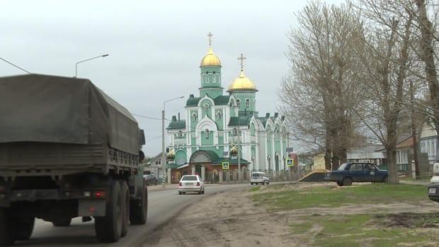 A Russian army truck drives past an Orthodox church on the main street of Maslovka.
