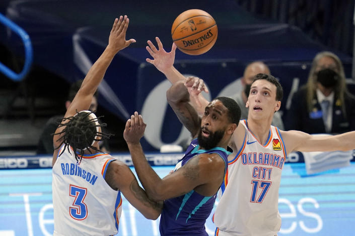 Charlotte Hornets guard Brad Wanamaker, center, passes between Oklahoma City Thunder guard Justin Robinson (3) and forward Aleksej Pokusevski (17) in the first half of an NBA basketball game Wednesday, April 7, 2021, in Oklahoma City. (AP Photo/Sue Ogrocki)