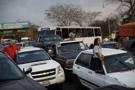 People wait with their vehicles at a checkpoint set up by Venezuelan security forces in Taguanes, Venezuela