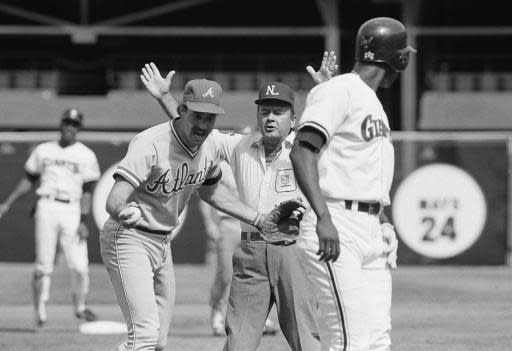 FILE - In this Sept. 10, 1984, file photo, Atlanta Braves' Randy Johnson, left, argues the call of safe at third base with second base umpire Dutch Rennert, center, as San Francisco Giants' Chili Davis looks back during a baseball game in San Francisco, Calif. Rennert, a National League umpire from 1973 to 1992 who was known for his animated, booming strike calls, has died. He was 88. St. John's Family Funeral Home and Crematory in St. Augustine, Florida, confirmed Monday night, June 18, 2018, that Rennert died on Sunday. A cause of death wasn't given. (AP Photo/Lui Wong, File)