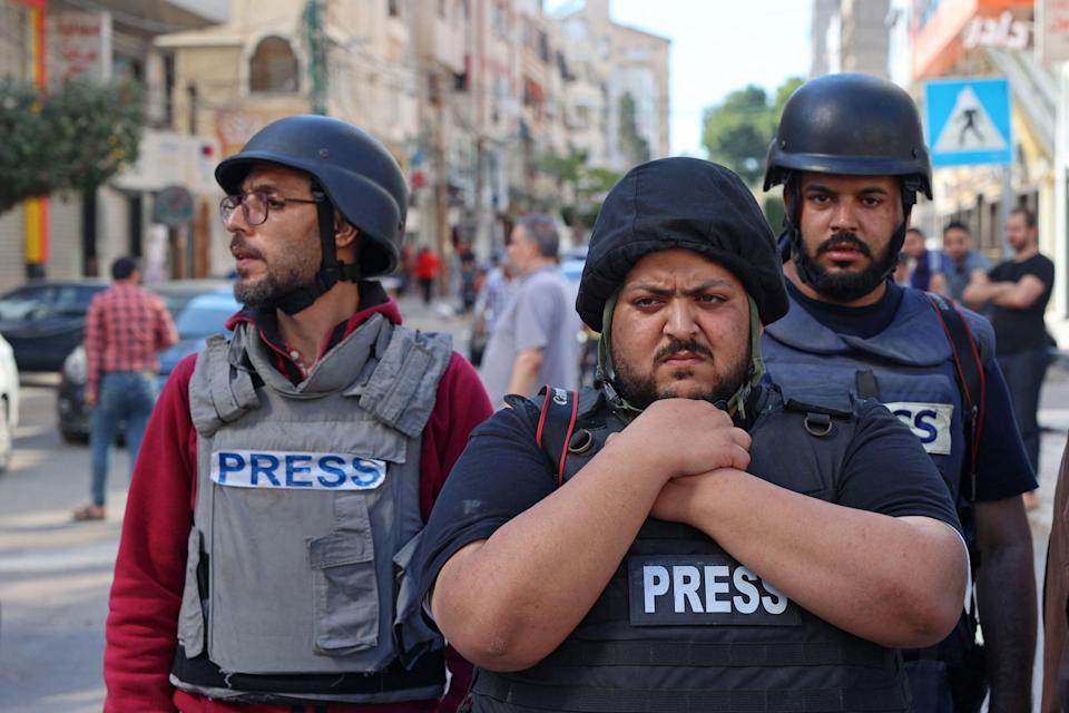 Palestinian journalists stand in shock following the destruction of Jala TowerAFP via Getty Images