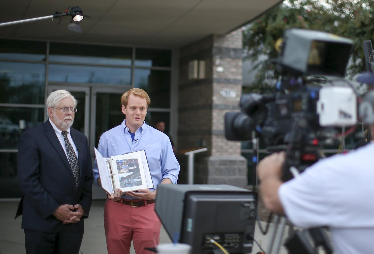 Chris Hurst (R), a journalist at the station and boyfriend of killed journalist Alison Parker shows a picture album that Parker put together for him as Jeff Marks (L), general manager for WDBJ7 look on as they speak with NBC's Today Show outside of the offices for WDBJ7 where killed journalists Parker and Adam Warm worked in Roanoke, Virginia August 27, 2015. The suspect in the on-air shooting of two Virginia television journalists was pronounced dead at a hospital on Wednesday (August 26), police said. The suspect Vester Flanagan, 41, shot himself after a police pursuit following the shooting of the journalists from CBS affiliate WDBJ7 in Roanoke, Virginia. Police pursued the suspect and in the late morning, local media and CNN reported the suspected shooter had shot himself. He was transported from the scene by ambulance but was later pronounced dead at hospital. REUTERS/Chris Keane