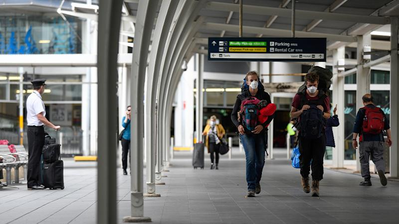 People are seen wearing masks after arriving at Sydney's airport. Source: AAP