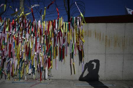 A visitor takes photographs of military fences decorated with ribbons, on which people have written their hopes for peace and reunification of the divided Korean peninsula, at the Imjingak pavilion near the demilitarized zone which separates the two Koreas, in Paju, north of Seoul October 16, 2013. REUTERS/Kim Hong-Ji