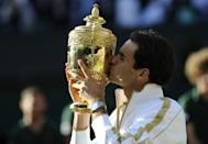 Marathon man: Federer kisses the trophy after his five-set win over Andy Roddick in 2009