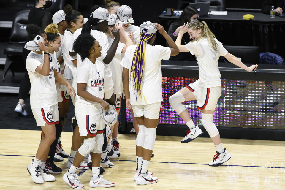 FILE - Connecticut's Paige Bueckers, right, dances over to teammates while celebrating an NCAA college basketball game win in the Big East tournament finals against Marquette at Mohegan Sun Arena in Uncasville, Conn, in this Monday, March 8, 2021, file photo. Paige Bueckers is in a class all by herself. UConn's star guard became the first freshman ever to win The Associated Press women's basketball player of the year award Wednesday, March 31, 2021. (AP Photo/Jessica Hill, File)