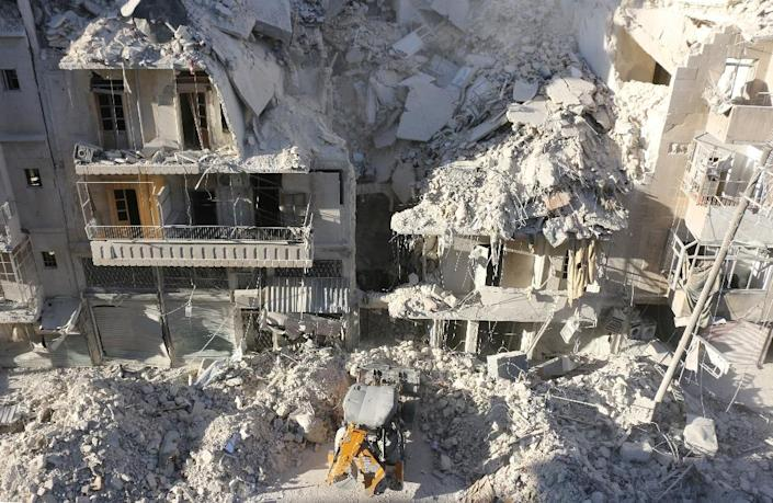 A tractor clears the rubble following Syrian govermnet forces air strikes in a rebel-held neighborhood of Aleppo on September 24, 2016 (AFP Photo/Thaer Mohammed)