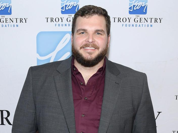 Jake Hoot wearing a gray blazer and red shirt in front of a white and blue background