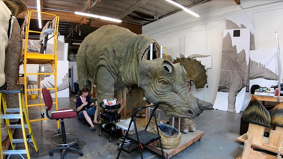 """Fabricator Tara Reich sews a leg on one of the dinosaurs that will be part of the new """"Jurassic World Live Tour."""""""