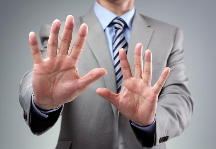 A businessman in a suit putting his hands up as if to say, no thanks.