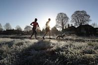 <p>People jogging with a dog along a frosty path in Cock Marsh, near Cookham, Berkshire. (PA) </p>