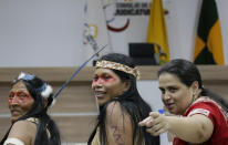 Waoranis leader Nemonte Nenquimo, center, and lawyer Lina Espinosa, right, wait for the start of a hearing on a lawsuit filed by the Waoranis against the Ministry of Non-Renewable Natural Resources for opening up oil concessions on their ancestral land, in Puyo, Ecuador, Friday, April 26, 2019. The judge went on to rule in favor of the Waoranis. (AP Photo/Dolores Ochoa)