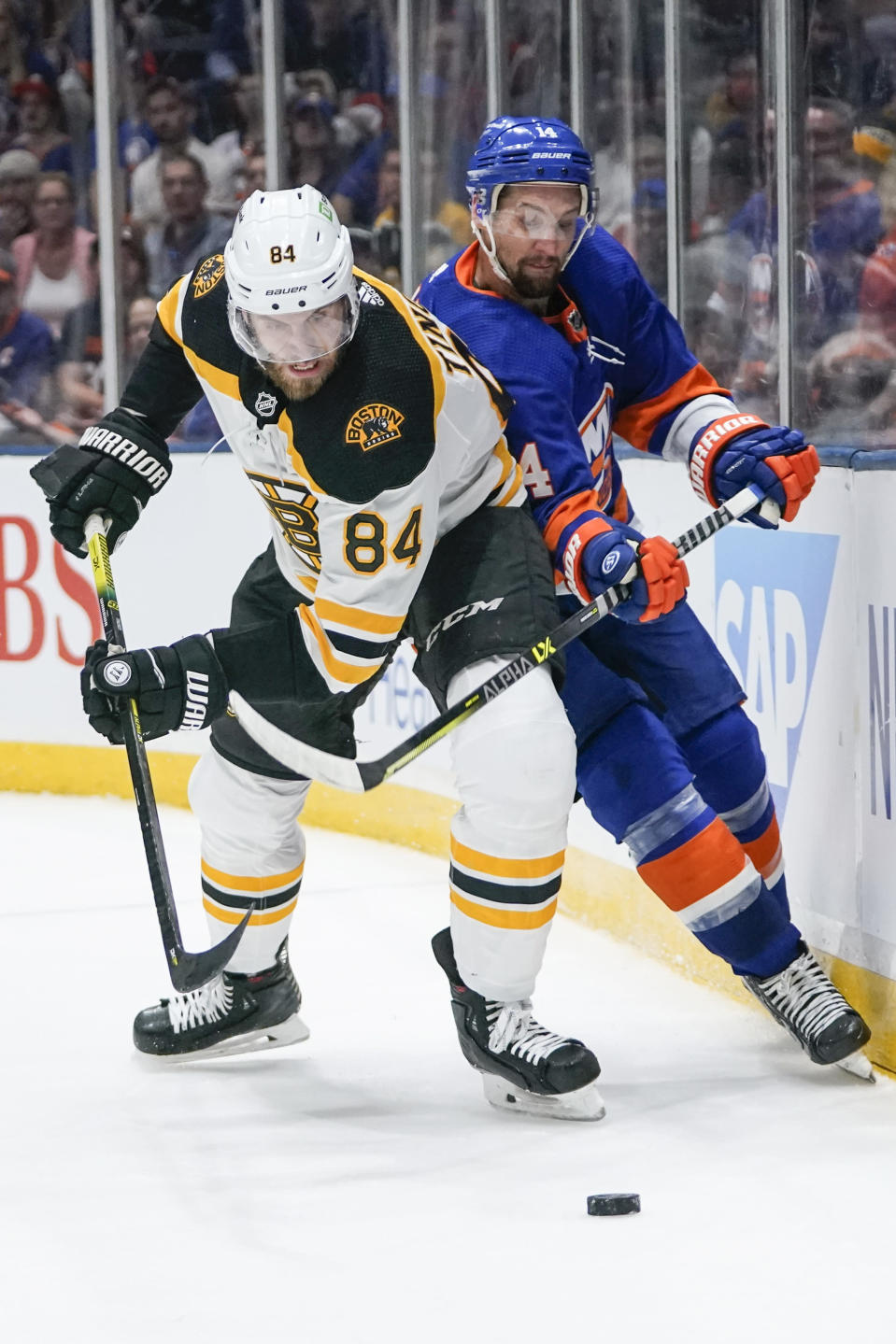 Boston Bruins' Jarred Tinordi (84) fights for control of the puck with New York Islanders' Travis Zajac (14) during the second period of Game 4 during an NHL hockey second-round playoff series Saturday, June 5, 2021, in Uniondale, N.Y. (AP Photo/Frank Franklin II)
