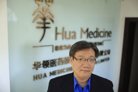 Li Chen, co-founder and CEO of Hua Medicine, poses for a photograph in front of a company logo, at his office in Shanghai, February 11, 2015. REUTERS/Aly Song