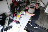 Belgian Yves Hanoulle, IT professional, walks on a treadmill installed under his desk, with the average of 20km daily, as he works in his home in Ghent