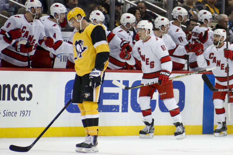 Pittsburgh Penguins' Brian Dumoulin, left, skates to the bench as Carolina Hurricanes' Jake Gardiner (51) is greeted by teammates after giving his team the lead with a goal during the second period of an NHL hockey game, Sunday, March 8, 2020, in Pittsburgh. (AP Photo/Keith Srakocic)