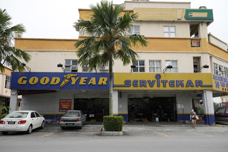 A woman wearing a face mask walks near a Goodyear shop in Bukit Jalil, outskirts of Kuala Lumpur, Malaysia, Friday, June 11, 2021. A Malaysian court on Thursday ruled in favor of 65 migrant workers who sued U.S. tiremaker Goodyear for underpaying them, their lawyer said, calling it a victory for foreign employees. (AP Photo/Vincent Thian)