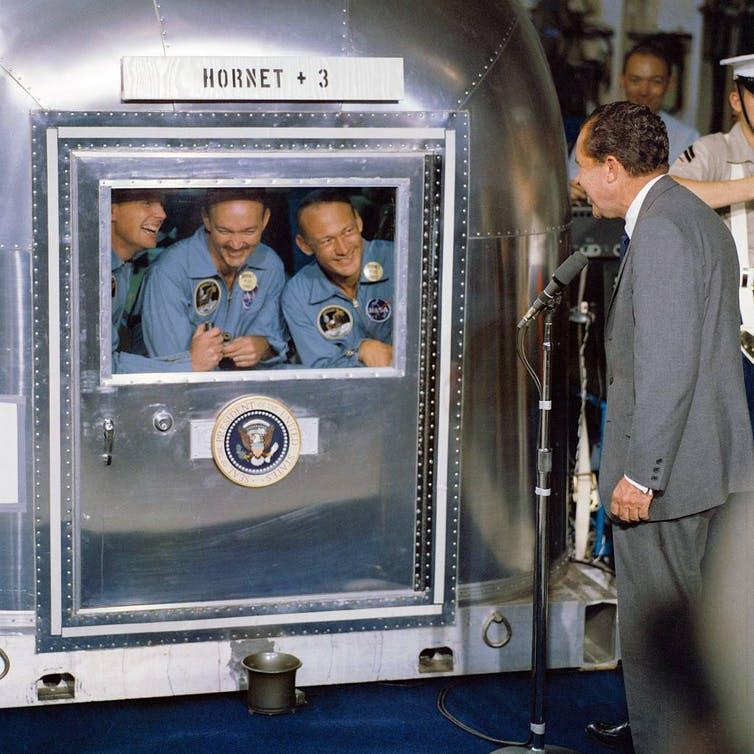 Apollo 11 astronauts in a small metal quarantine facility, with President Richard M. Nixon speaking to them from outside.