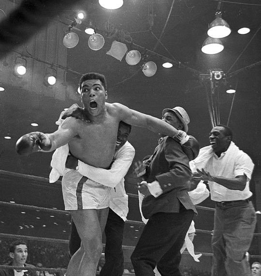 <p>Cassius Clay's handlers hold him back as he reacts after he is announced the new heavyweight champion of the world on a seventh round technical knockout against Sonny Liston at Convention Hall in Miami Beach, Fla., on Feb. 25, 1964. (AP Photo)</p>