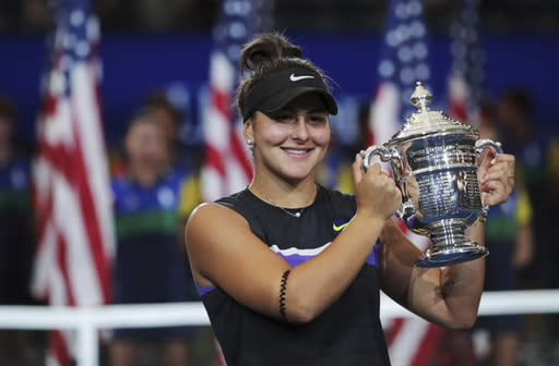 FILE - In this Sept. 7, 2019, file photo, Bianca Andreescu, of Canada, holds up the championship trophy after defeating Serena Williams, of the United States, in the women's singles final of the U.S. Open tennis championships in New York. The U.S. Tennis Association intends to hold the U.S. Open Grand Slam tournament in New York starting in August without spectators, if it gets governmental support -- and a formal announcement could come this week.(AP Photo/Charles Krupa, File)
