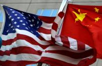 National flags of U.S. and China wave in front of an international hotel in Beijing
