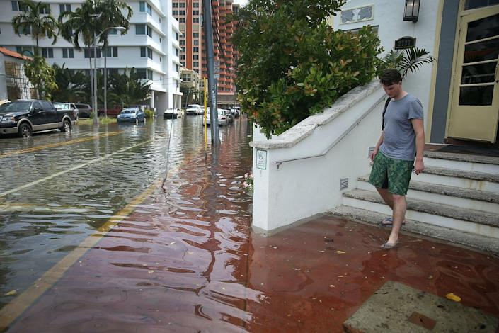 A man wearing flipflops steps onto a **flooded** sidewalk while leaving a hotel.