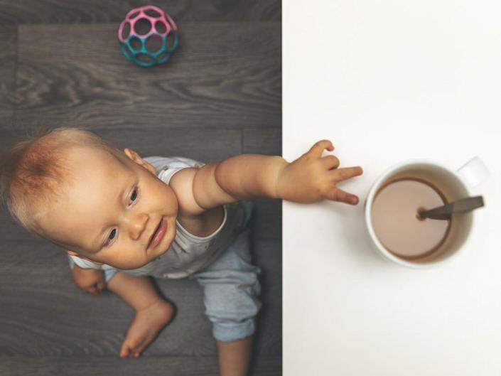 A child reaches up for a cup of coffee.