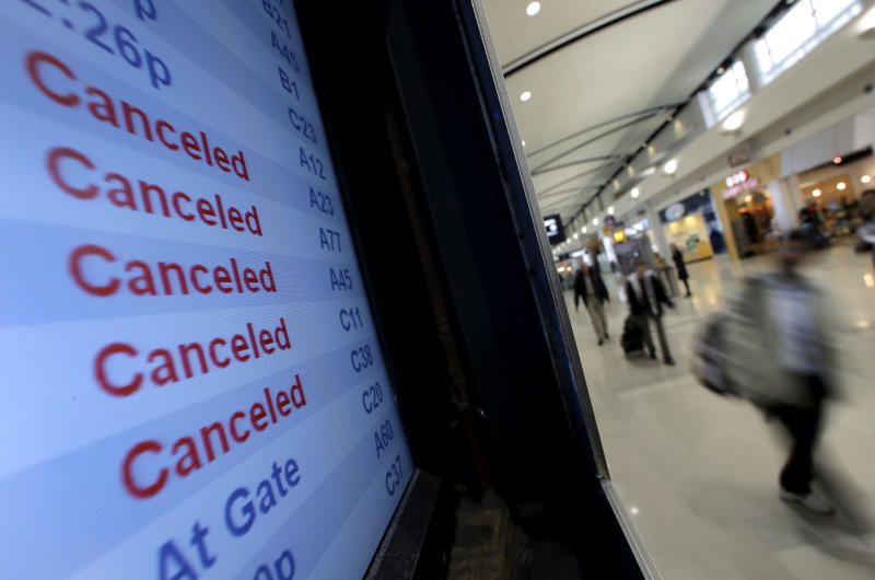 Travelers on Delta Airlines look at a departure screen Monday, Oct. 29, 2012, in Detroit. Dozens of departing flights have been canceled at Detroit Metropolitan Wayne County Airport as a looming superstorm locks down flights to the East Coast. Hurricane Sandy continued on its path Monday, as the storm forced the shutdown of mass transit, schools and financial markets, sending coastal residents fleeing, and threatening a dangerous mix of high winds and soaking rain.  (AP Photo/Charlie Riedel)