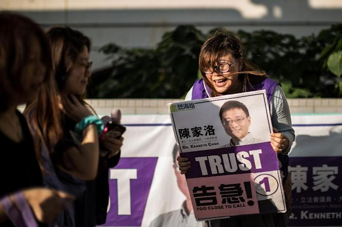 A campaigner (R) for election candidate Kenneth Chan of the Civic Party greets passing pedestrians near a polling station in the Southern district of Hong Kong on November 22, 2015 (AFP Photo/Anthony Wallace)