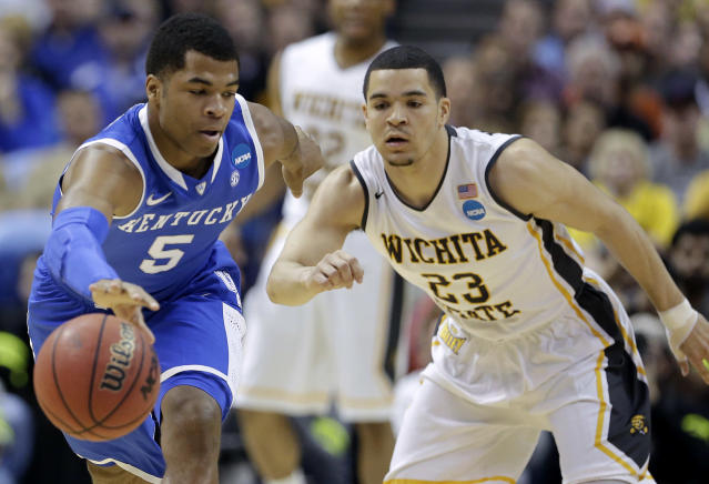 Kentucky guard Andrew Harrison (5) and Wichita State guard Fred VanVleet (23) go for a loose ball during the first half of a third-round game of the NCAA college basketball tournament Sunday, March 23, 2014, in St. Louis. (AP Photo/Charlie Riedel)