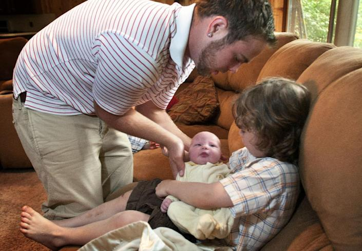 In this Aug. 6, 2013, photo, Tyler Schwandt, left, shows younger brother Wesley how to support newborn Tucker's head in their home in Rockford, Mich. Jay and Kateri Schwandt welcomed their 12th child this week _ and they're all boys. (AP Photo/MLive.com, The Grand Rapids Press, Chris Clark)