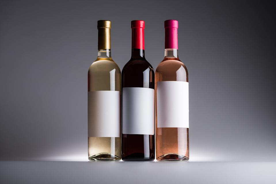bottles of red, white and rose wine with blank labels on dark background with back light