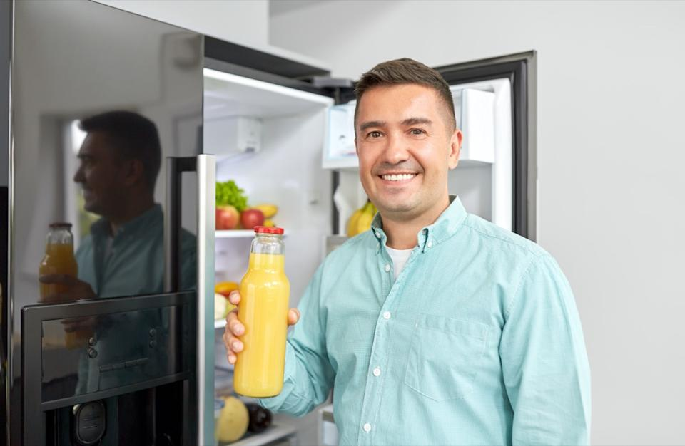 middle-aged man taking bottle of orange juice from fridge at home kitchen