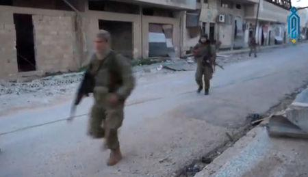 A still image taken from a video uploaded on social media on March 22, 2017, purports to show Tahrir al-Sham rebel fighters running with their weapons, said to be in Soran district, near Hama, Syria. Social Media Website via Reuters TV