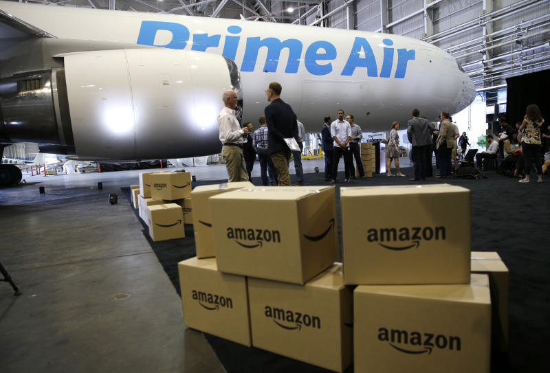 "FILE - In this Aug. 4, 2016 file photo, Amazon.com boxes are shown stacked near a Boeing 767 Amazon ""Prime Air"" cargo plane on display in a Boeing hangar in Seattle. Amazon's Prime shipping program set the pace for shoppers' expectations, and the nation's largest online player continues to look for new ways to keep up with shoppers' demands. (AP Photo/Ted S. Warren, File)"