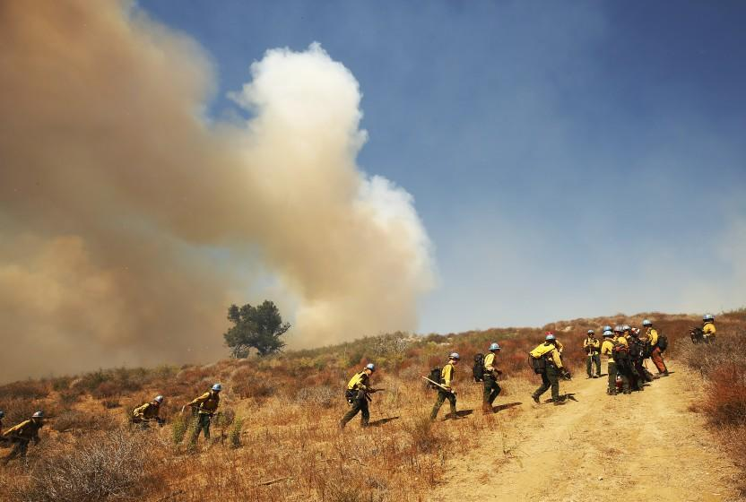GAVIOTA COAST, CA - OCTOBER 12: Firefighters from California Conservation Corps prepare as flames from the Alisal Fire move toward La Paloma Ranch near Refugio Canyon Tuesday afternoon. Rancher Eric Hvolboll remembers the 2016 Sherpa Fire where he lost many avocado trees and broke a leg during g the blaze that burned through his La Paloma Ranch. The Alisal Fire is over 7,000 acres on Tuesday after it quickly grew Monday afternoon driven by sundowner winds as it burned through Tajiguas Canyon to the 101 freeway forcing its closure. Mandatory evacuations are in place as the gusty winds drive flames through rough terrain that hasn't burned in decades. The 1955 Refugio Fire that consumed 80,000 acres is the last time much of the area had burned. The historic Reagan Rancho del Cielo which sits near the top of Refugio Canyon could be threatened by the flames as the fire moves into Refugio Canyon. Refugio Road on Tuesday, Oct. 12, 2021 in Gaviota Coast, CA. (Al Seib / Los Angeles Times).