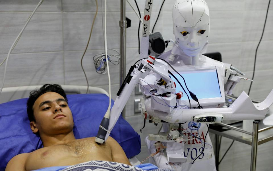 A volunteer is examined by Cira 3, a remote-controlled robot that runs tests on suspected coronavirus disease - Mohamed Abd El Ghany/Reuters