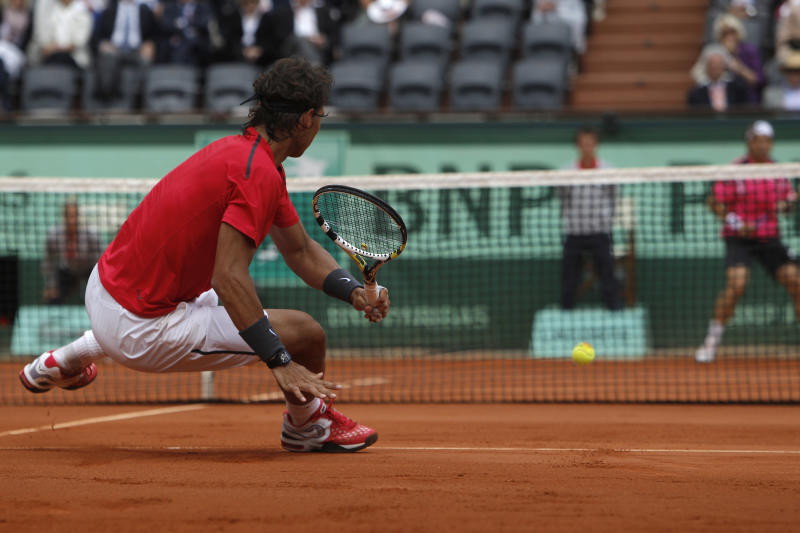 Rafael Nadal of Spain slips as he returns in his semi final match against compatriot David Ferrer, rear right, at the French Open tennis tournament in Roland Garros stadium in Paris, Friday June 8, 2012. (AP Photo/Michel Spingler)