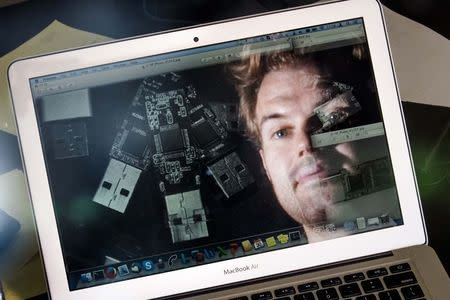 German crypto specialist and and chief scientist with Berlin's SR Labs Karsten Nohl is reflected in a computer screen as he looks at photographs of USB sticks in his office in Berlin, July 30, 2014. REUTERS/Thomas Peter