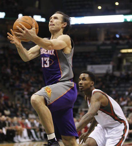 Phoenix Suns' Steve Nash (13) puts up a shot in front of Milwaukee Bucks' Brandon Jennings, right, during the first half of an NBA basketball game Tuesday, Feb. 7, 2012, in Milwaukee. (AP Photo/Jeffrey Phelps)