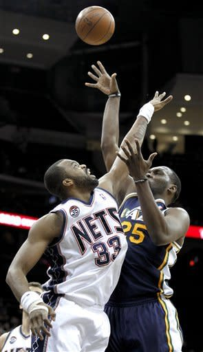 New Jersey Nets' Shelden Williams (33) defends on a shot by Utah Jazz's Al Jefferson in the first quarter of an NBA basketball game, Monday, March 26, 2012, in Newark, N.J. (AP Photo/Julio Cortez)