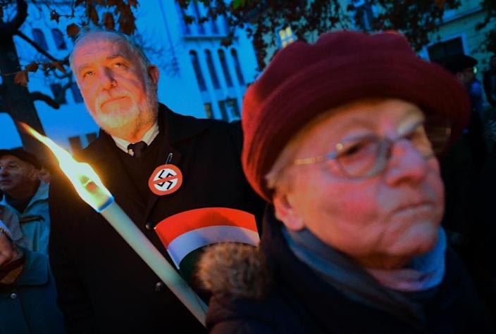 A protestor (L) wearing a button with a crossed-out swastika holds a torch in the town of Szekesfehervar, Hungary on December 13, 2015 at a rally against a planned statue of World War II politician Balint Homan, an architect of anti-Jewish laws (AFP Photo/Attila Kisbenedek)