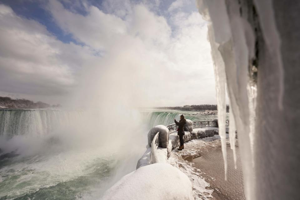 A woman takes a photo at the Horseshoe Falls in Niagara Falls, Ontario, on January 27, 2021. (Photo by Geoff Robins / AFP) (Photo by GEOFF ROBINS/AFP via Getty Images)